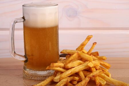 bocal: One big glass bocal of light cold delicious beer with white froth and tasty crispy yellow potato fasfood chips on wooden background closeup, horizontal picture