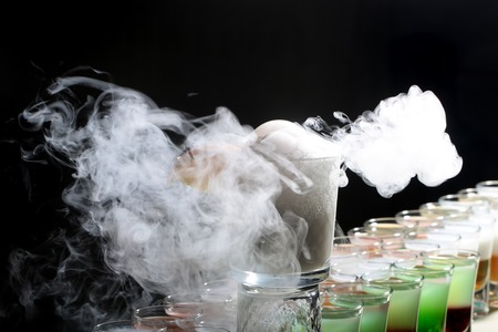 Colorful alcoholic shot cocktails in glasses and one long beverage making reaction of white smoke standing in row on black studio background, horizontal picture