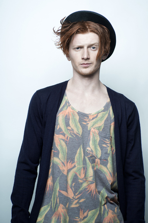 young unshaven: One attractive red haired young fashionable unshaven stylish man in underwear with colorful floral print black hat and blue jersey standing in studio on white background, vertical picture