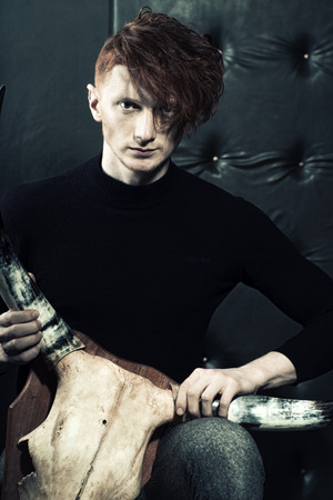 young unshaven: One handsome red haired young stylish unshaven man in jersey and grey trousers holding animall scull head with antlers sitting in studio on black leather background, vertical picture Stock Photo