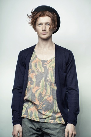 young unshaven: One handsome red haired young fashionable unshaven stylish man in underwear with colorful floral print black hat and blue jersey standing in studio on white background, vertical picture
