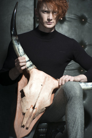 young unshaven: One attractive red haired young stylish unshaven man in jersey and grey trousers holding animall scull head with antlers sitting in studio on black leather background, vertical picture