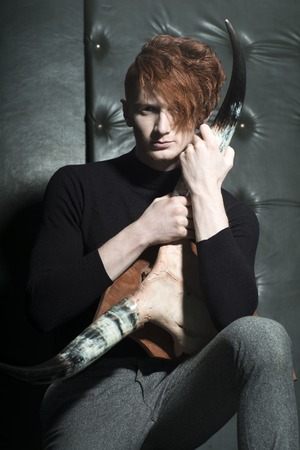 One handsome red haired young fashionable unshaven man in jersey and grey trousers holding animall scull head with antlers sitting in studio on black leather background, vertical picture