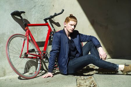 young unshaven: One cute red haired young fashionable unshaven stylish man in blue jacket sitting outdoor in street sunny day near bycicle leaning on grey wall, horizontal picture