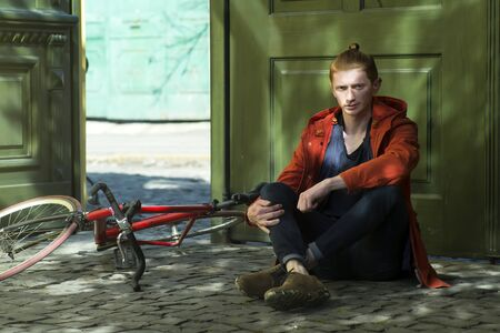 cycler: One cute red haired young fashionable unshaven stylish man in prange jumper sitting outdoor in street sunny day near green door and bycicle lying on ground, horizontal picture
