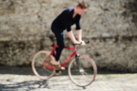 bycicle: Blurred background of one young active red haired man training on bycicle outdoor sunny day on grey stony wall background, horizontal picture