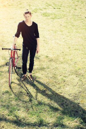cycler: One young handsome red haired fashionable unshaven boy standing with bycicle on fresh green grass on lawn relaxing listening music in white head-phones sunny day outdoor copyspace, vertical picture