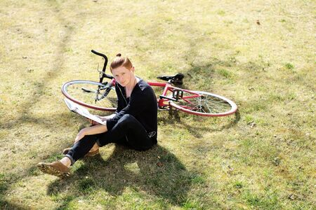young unshaven: One young handsome red haired fashionable unshaven man sitting with bycicle on fresh green grass on lawn relaxing listening music in white head-phones sunny day outdoor, horizontal picture