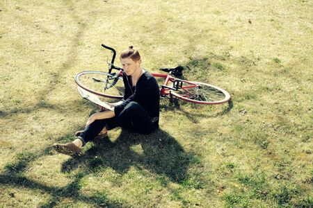 cycler: One young attractive red haired fashionable unshaven man sitting with bycicle on fresh green grass on lawn relaxing listening music in white head-phones sunny day outdoor, horizontal picture