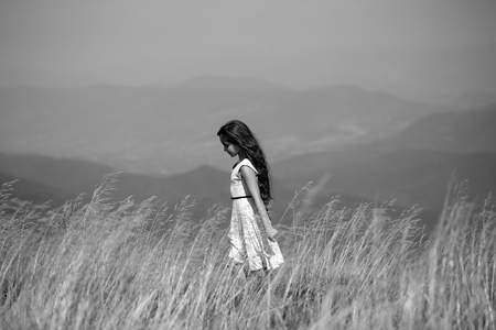 spaciousness: Back viev of young pretty girl in lace summer dress walking in mountain valley with deep dry spikelet grass in spring sunny day outdoor on natural background black and white, horizontal picture