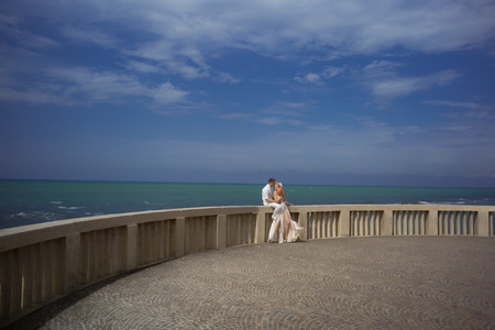 gauzy: Beautiful wedding couple of blonde standing woman in long gauzy dress and man in white sitting on stony balcony parapet of big terrace on emeral ocean water and blue sky background, horizontal picure Stock Photo