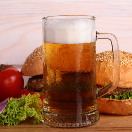 near beer: Few fresh tasty burgers of green lettuce meat cutlet tomato and white bun with sesame seeds near and glass of light beer with froth on octoberfest holiday on wooden background, square picture Stock Photo