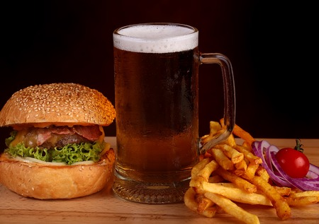 near beer: resh tasty burger of green lettuce meat cutlet cheese tomato and white bread bun with sesame seeds near chips and glass of dark beer on octoberfest holiday on black background, horizontal picture