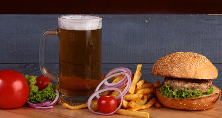 near beer: Big fresh tasty burger of green lettuce meat cutlet cheese tomato and white bread bun with sesame seeds near chips and glass of light beer on octoberfest holiday on grey background, horizontal picture Stock Photo