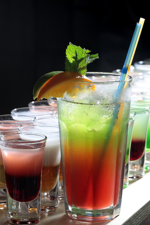 cold drinks: Many alcoholic tasty hard shot cocktails in drinking glasses and one long beverage with straws and orange green brown red and white colors standing in row on black studio background, vertical picture Stock Photo