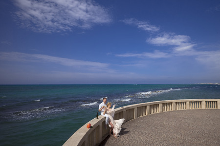 gauzy: Wedding couple of woman in long dress and man in white drinking wine of bottle on balcony parapet of big terrace with rose flower bunch on ocean water and blue sky background, horizontal picure