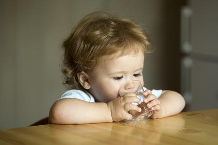 少し深刻なかわいい魅力的な素敵な子美少年瞳と飲料水を持って小さなガラスから手に屋内のテーブルに座っている巻き毛ぼかし灰色の背景は、水 写真素材