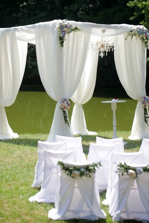 arranging chairs: Beautiful decorated with light white chiffon chandelier and bouquets of roses pastel colors wedding pavilion chairs and table standing on green grass near lake and trees sunny day, horizontal picture