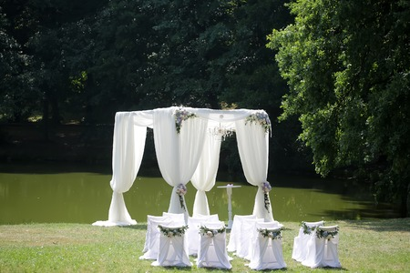 marriage: Beautiful decorated with light white chiffon chandelier and bouquets of roses pastel colors wedding pavilion chairs and table standing on green grass near lake and trees sunny day, horizontal picture