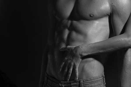 nude breasts: Closeup of naked sexual man with beautiful wet muscular body and female hands touching male six-pack standing in studio black and white, horizontal picture Stock Photo