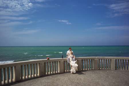 gauzy: Wedding pair of woman in long dress and man in white drinking wine of bottle on balcony parapet of big terrace with rose flower bouquet on ocean water and blue sky background, horizontal picure Stock Photo