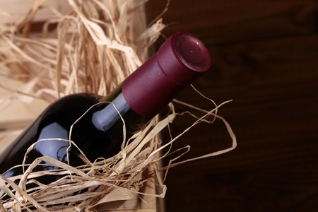 One luxury full dark glass bottle of red expensive collection grape wine in gift wooden box with straw, horizontal photo