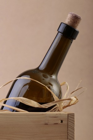 not full: Closeup photo of uncorked not full dark glass bottle of vintage red wine in wooden box with straw, vertical picture Stock Photo