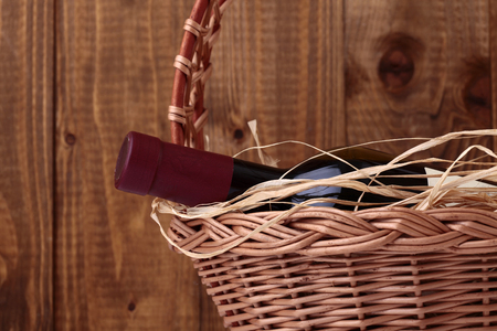 corked: One vintage corked glass bottle of red wine with label decorated with straw lies in gift wicker basket on wooden planks wall background, horizontal photo