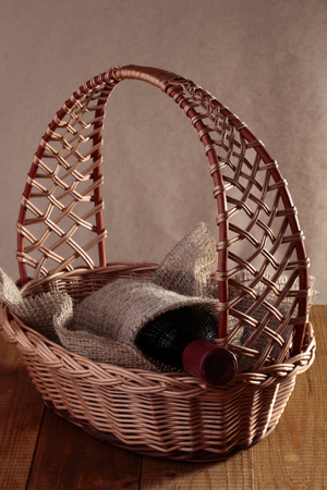 corked: Corked glass vintage unlabel bottle of fragrant red wine wrapped piece of burlap lies in original wicker gift basket on wooden table, vertical picture Stock Photo
