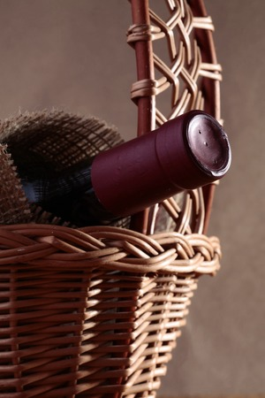 closed corks: Closeup photo of closed dark glass unlabels bottle of brand red wine covered with burlap in beautiful wicker gift basket, vertical picture Stock Photo