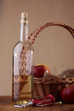 semisweet: Composition of uncorked unlabel transparent glass bottle of aromatic sweet white wine wicker basket decorated with burlap apples and red corkscrew on brown wooden table, vertical photo Stock Photo
