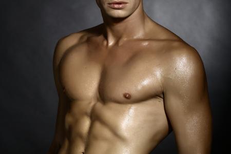 seins nus: Gros plan d'un jeune homme nu sexuelle avec une belle musculaire corps solide et le torse permanent humide en studio sur fond gris mur arri�re-plan, l'image horizontale