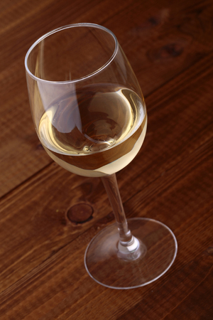 semisweet: Closeup photo of one full clear glass goblet with white semisweet grape wine standing on brown wooden table top, vertical picture