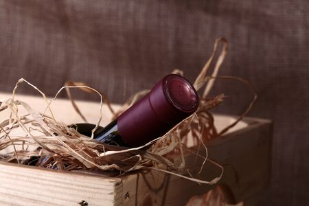 corked: One corked glass bottle of red expensive collection grape wine in wooden box with straw indoors, horizontal photo Stock Photo