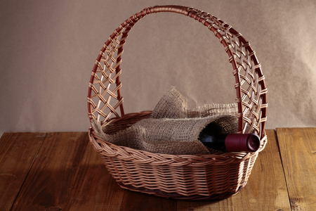 corked: Beautiful wickerwork gift basket with expensive corked glass bottle good quality red wine wrapped piece of burlap on wooden table, horizontal photo