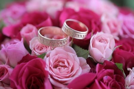Primo piano di una bella rosa fresca e rosa rossa mazzo di fiori con due anelli d'oro di nozze, maschera orizzontale Archivio Fotografico - 45164190