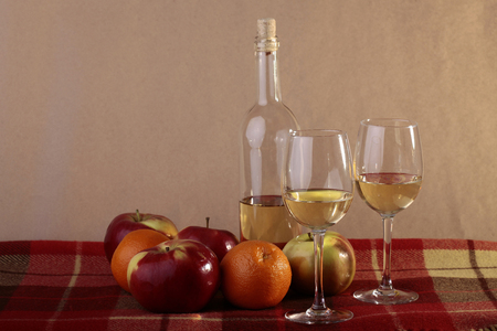 semisweet: Still life of uncorked transparent glass bottle of semisweet white wine with two filled glasses ripe apples oranges on table covered with red plaid, horizontal photo