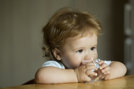 Handsome serious sweet little boy child with brown hair hazel eyes looking away sitting at table drinking water from small glass holding by hands indoor on blur grey background closeup, horizontal Foto de archivo