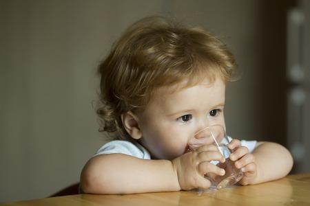 tomando agua: Hermoso serio dulce ni�o ni�o con el pelo marr�n avellana ojos que miran lejos que se sientan en el agua potable de la mesa peque�a celebraci�n de vidrio por las manos de interior en difuminar primer gris del fondo, horizontal