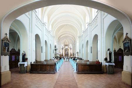Wedding ceremony in spacious bright columned hall of Catholic Church with wooden pews decorated elegant white bows, horizontal photo