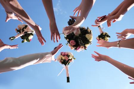 Vrouwen handen probeert te vangen vier mooie bruiden boeketten van rozen pastel kleuren op heldere blauwe hemel achtergrond, horizontale foto Stockfoto