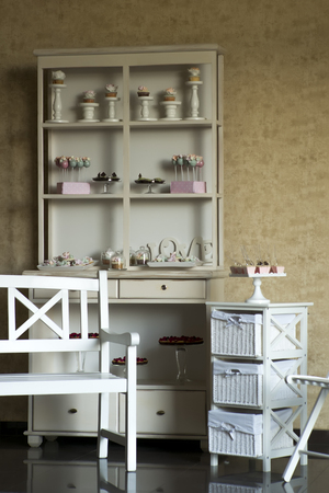 commode: Vintage white wooden buffet with beautifull packaged candy cakes maffins stand with sweets on commode with baskets bench and chair, vertical photo Stock Photo