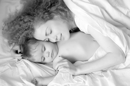 Closeup of young smiling loving mother with soft curly hair embracing small tiny cute male lovely baby sleeping indoor in bed with white linen black and white, horizontal picture 版權商用圖片