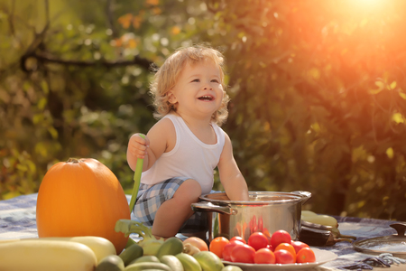 marrow squash: One laughing boy at picnic sitting with ladle pot orange pumpkin red tomato squash and cucumber playing with food sitting on blue checkered plaid on natural background sunny day, horizontal picture