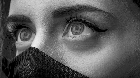 nude young: Portrait of one beautiful sensual woman with big eyes and face covered with very thin cobwed fabric looking away black and white closeup, horizontal picture