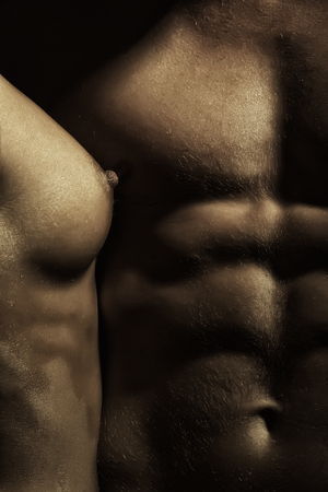 naked black men: Closeup of stripped sensual man with beautiful muscular body and female nipple of young woman with bare chest near male six-pack standing close to each other, vertical picture Stock Photo