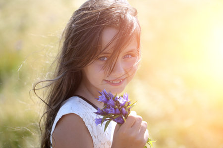 field of flowers: Portrait of pretty young brunette smiling girl with long hair in white lace dress holding violet field flowers looking forward standing in valley with spikelet sunny day outdoor, horizontal photo