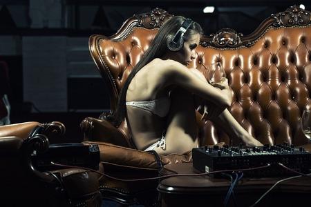 party dj: dj chica de glamour joven atractiva con maquillaje brillante en ropa interior y auriculares sentado en el sofá de cuero marrón real a la mesa con la consola del mezclador sosteniendo copa de vino en el club de noche de interior, cuadro horizontal
