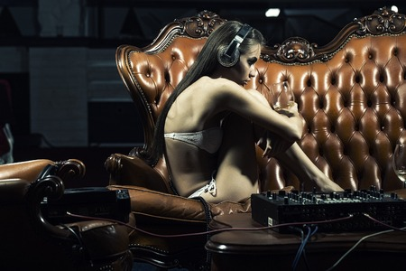 dj mixer: Sexy young glamour dj girl with bright make-up in underwear and headphones sitting on brown leather royal sofa at table with mixer console holding wine glass in night club indoor, horizontal picture