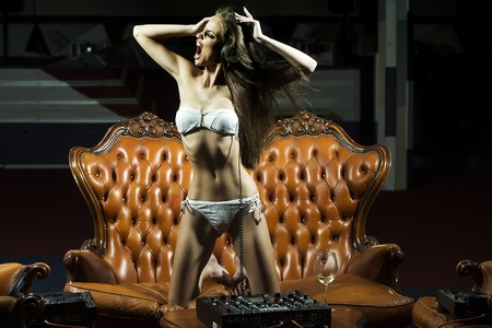 underwear: Sexy glamour shouting dj girl with bright make-up in underwear and headphones standing near brown leather royal sofa table with mixer console and wine glass in night club indoor, horizontal picture Stock Photo